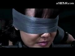 Busty girl tied to metal frame blindfolded getting her soles tortured in the dungeon