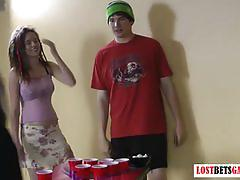 Three girls and one guy play a game of strip beer pong