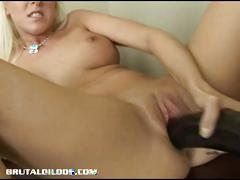 This blonde babe forces a massive brutal dildo in her tight pussy