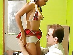 Pigtailed petite schoolgirl in stockings and a miniskirt fucked on a desk