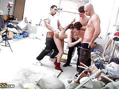 Slim brunette getting gang drilled in a workshop