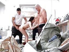 Slim brunette getting gang drilled in a workshop
