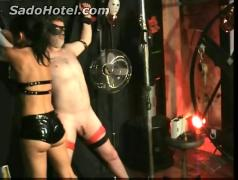 Horny mistress with nice tits and great body ties masked slave to a wall and puts sticks in his cock