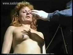 German master removes needles from slave her body and uses a candle to drop hot wax on her tits