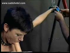 Slave with metal clamps on her nipples and her face and body covered with candlewax is sucking