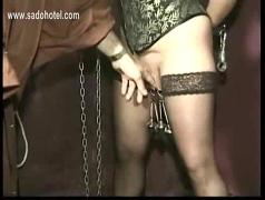 Hangin slave with big boobs gets large metal clamps on her nipples and pussy lips while her master