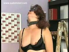 Milf slave with big tits is hit with a whip on her pussy is tied to a stepladder