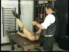 Slave with tiny tits lying on a table and metal clamps on her pussy lips