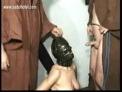 Slave wearing mask sucks cock while other master hits her tits and fucks him hard and gets a facial