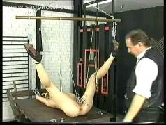 Hot slave lying with her legs spread and a rope around her nipples gets large metal clamps
