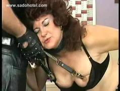 Milf slave in leather bending over a ladder is hit and spanked on her ass by master