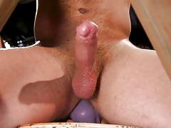 Muscular hunk riding gigantic anal dildo in the dungeon