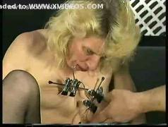 German slave with metal clamps on her pussy lips and tits is spanked on her cunt in a dungeon