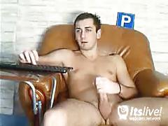 Sexy stud sitting on leather couch for webcam show