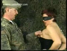 German drill instructor spanks ass of horny slave wearing latex thong and squeezes her boobs