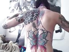 Tattooed muscle chick rubs oil all over body