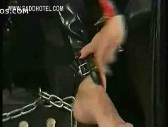 Dominatrix wearing latex uses her high heels on body of tied bdsm dirty masked slave