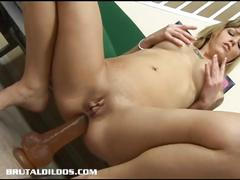 She shoves big dildo in her ass hole and rides it