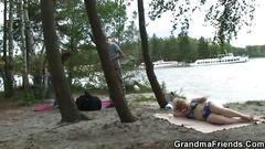 Chubby beach granny sucks two lads off