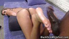 Oiled white feet give an interracial footjob