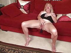 Gorgeous mature lady poses and rubs herself on red couch