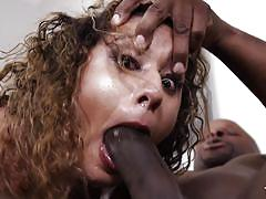 Curly haired babe getting throat-fucked by a black cock
