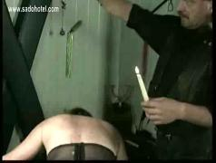 Naked slave gets her back and ass covered in hot candlewax by master bdsm